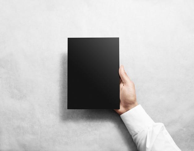 Mano que sostiene la maqueta de folleto de folleto negro en blanco