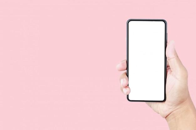 Mano que sostiene la maqueta del smartphone en fondo en colores pastel rosado con el espacio de la copia