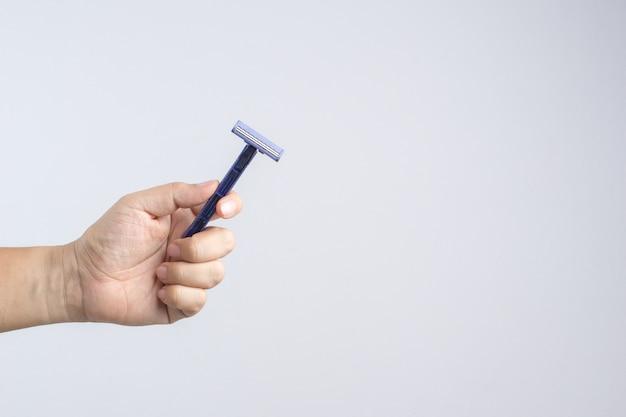 Mano que sostiene la maquinilla de afeitar desechable y barata