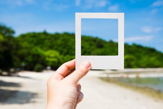 Mano que sostiene el marco de foto instantánea en la playa