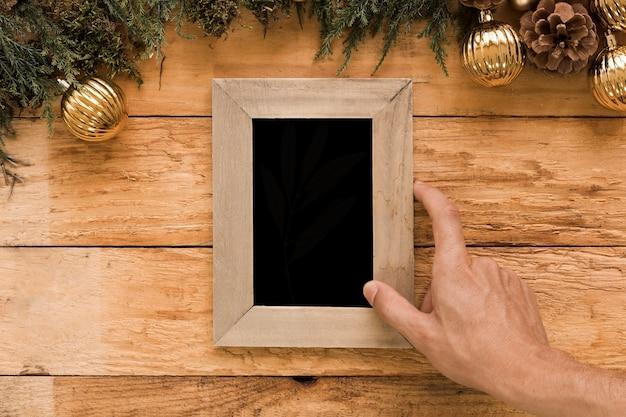 Mano que sostiene el marco de fotos cerca de ramitas de coníferas y bolas de navidad