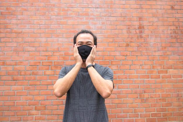 La mano que sostiene la máscara en la pared de ladrillo de fondo de cara de hombre asiático.