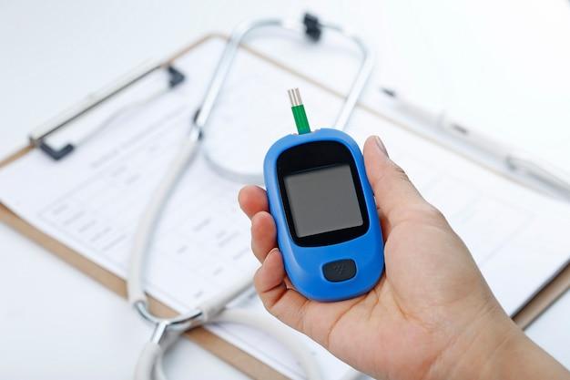 Mano que sostiene un medidor de glucosa de sangre que mide el azúcar de sangre, el fondo es un estetoscopio y un archivo de carta