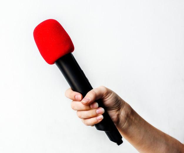 Mano que sostiene el micrófono aislado en el fondo