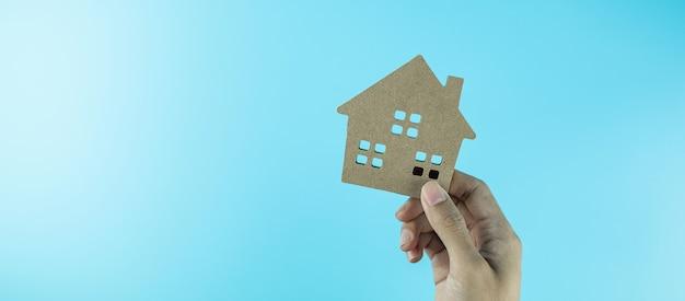 Mano que sostiene el modelo de la casa. conceptos bancarios, inmobiliarios, de inversión, financieros y de ahorro.
