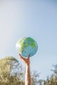 Mano que sostiene el modelo inflable del planeta