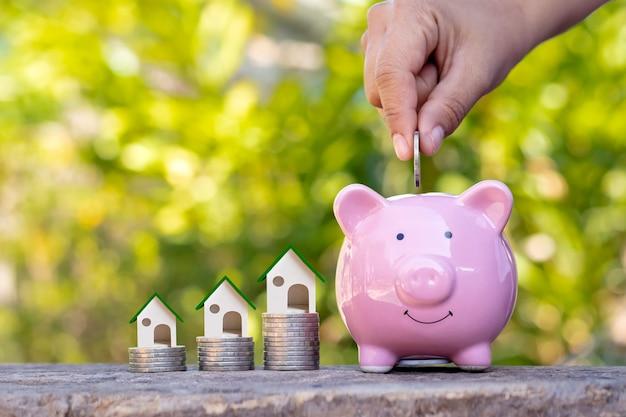 Mano que sostiene la moneda en la hucha de cerdo y el diseño de la casa en el montón de monedas concepto de dinero inversión y negocios inmobiliarios