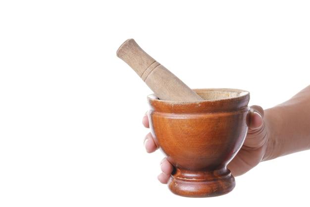 Mano que sostiene mortero de madera y maja de madera