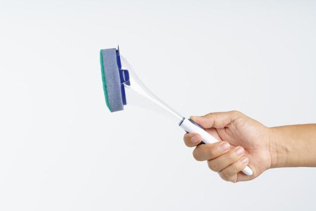 Mano que sostiene el nuevo cepillo de esponja con mango de plástico
