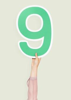 Mano que sostiene el número nueve signo
