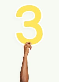 Mano que sostiene el número tres signo