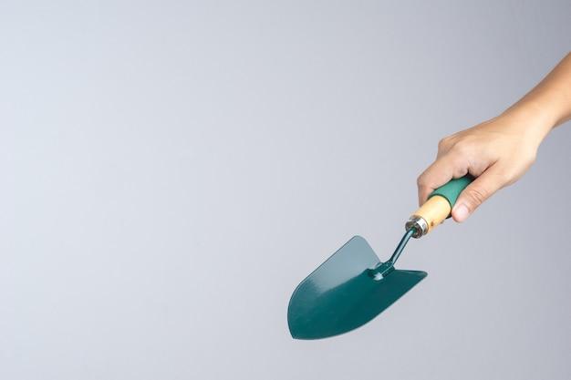 Mano que sostiene la pala de jardín verde con mango de madera