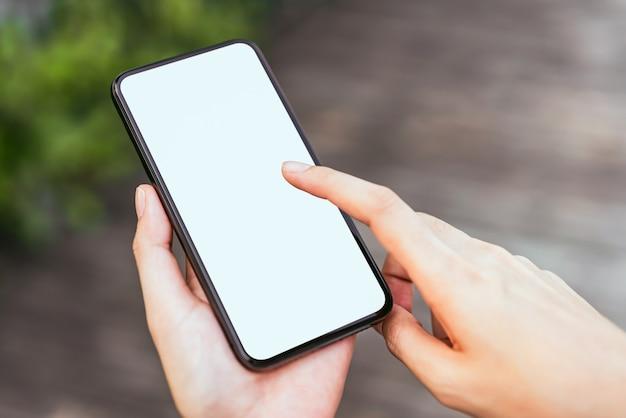 Mano que sostiene la pantalla en blanco del teléfono inteligente