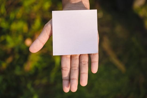 Mano que sostiene el papel en blanco sobre fondo de naturaleza.