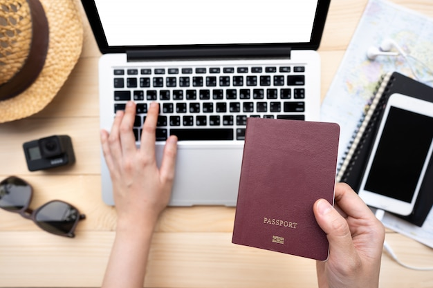 Mano que sostiene el pasaporte con un mapa y una computadora portátil para planear viajar.