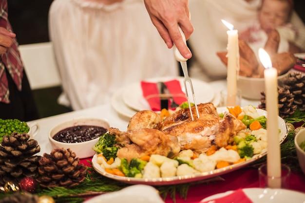 Mano que sostiene el pavo con un tenedor en la mesa de navidad