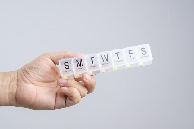 Mano que sostiene la píldora semanal de plástico o caja de medicina con braille
