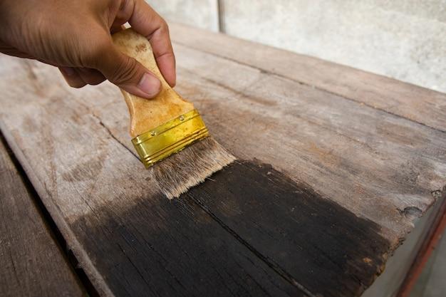 Mano que sostiene un pincel pintar la superficie de los tableros de madera con tintes de madera