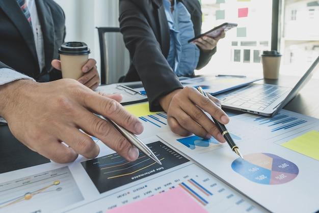 Mano que sostiene la pluma, la reunión del equipo de mujeres empresarias y empresarios para planificar estrategias para aumentar los ingresos comerciales