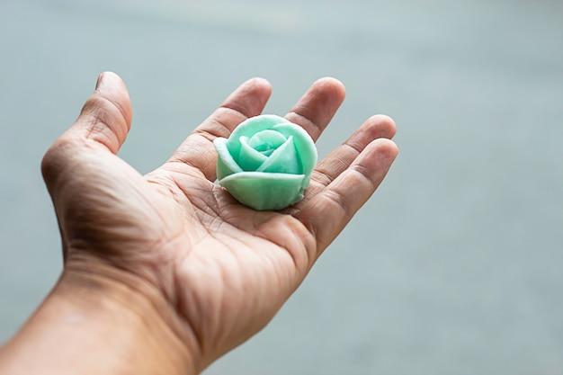 La mano que sostiene el postre de la flor del postre verde o dulce aalaw.