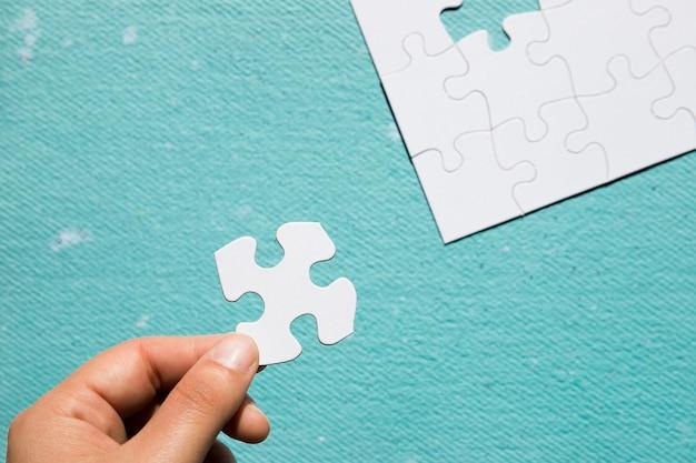 Mano que sostiene el rompecabezas blanco de cartón sobre fondo azul con textura