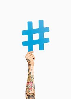 Mano que sostiene el símbolo del hashtag