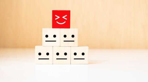Mano que sostiene el símbolo de la sonrisa y la cara triste en bloques de cubo de madera. concepto de emoción, calificación de servicio, clasificación, revisión del cliente, satisfacción y retroalimentación