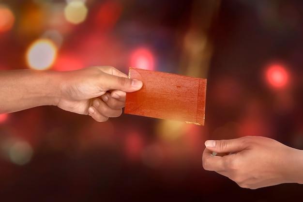 Mano que sostiene el sobre rojo chino