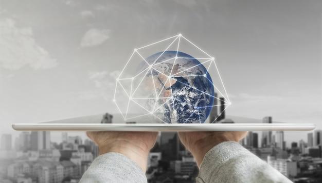 Mano que sostiene la tableta digital con tecnología de conexión de red global y edificios modernos