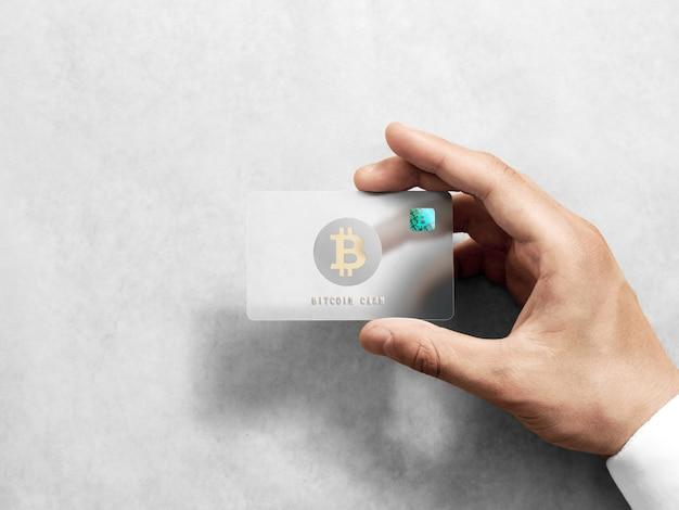 Mano que sostiene la tarjeta bitcoin con el logotipo de oro en relieve