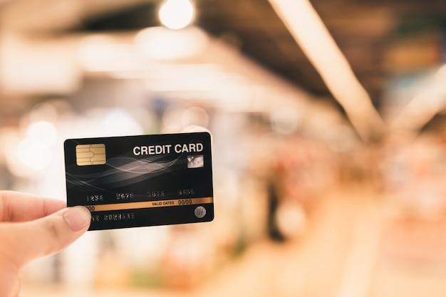 Mano que sostiene la tarjeta de crédito con concepto de supermercado borroso, compras y venta por menor