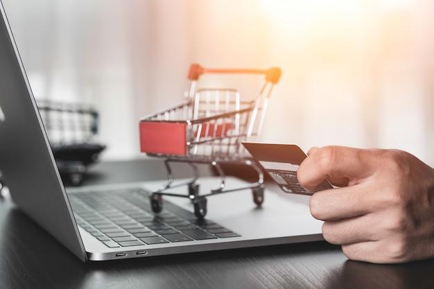 Una mano que sostiene la tarjeta de crédito y otra orden de entrada a la computadora portátil con fondo de carrito de compras. compras en línea y trabajo desde el concepto de hogar.