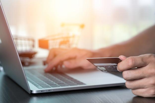 Una mano que sostiene la tarjeta de crédito y otra orden de entrada a la computadora portátil con fondo de tarjeta de compras. compras en línea y trabajo desde el concepto de hogar.
