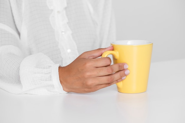 Mano que sostiene la taza amarilla sobre una mesa