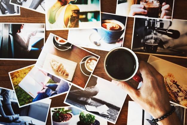 La mano que sostiene la taza de café con puede fotografiar sobre la mesa