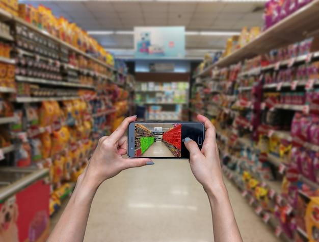Mano que sostiene la tecnología de la tableta comprobar productos de fábrica y almacén