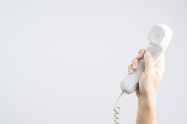 Mano que sostiene el teléfono de casa u oficina con línea