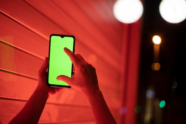 Mano que sostiene el teléfono celular con pantalla de cámara e iluminación nocturna
