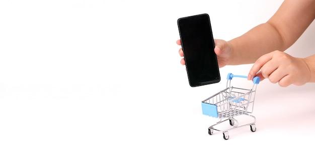 Una mano que sostiene el teléfono inteligente y empuja el carrito de la compra.