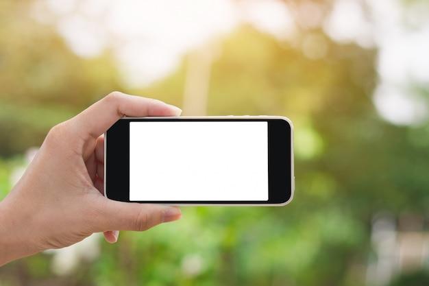 Mano que sostiene el teléfono inteligente en el fondo de la naturaleza con espacio de copia