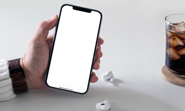Mano que sostiene el teléfono inteligente iphone 12 pro max y muestra la pantalla en blanco.