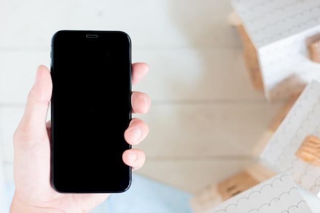 Mano que sostiene el teléfono inteligente con el libro de cuentas y el modelo de casa en miniatura