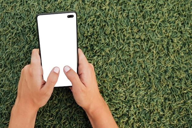 Mano que sostiene el teléfono inteligente moderno con maqueta