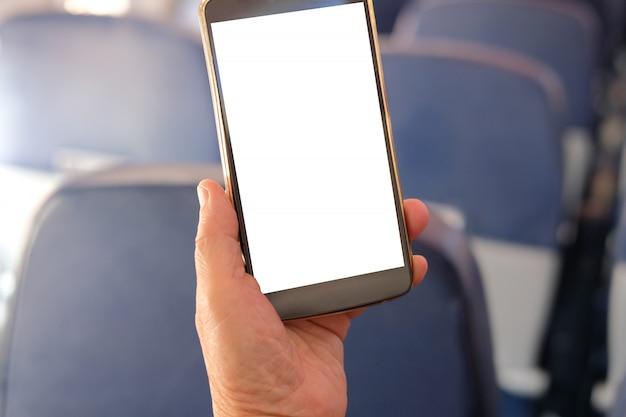 Mano que sostiene el teléfono inteligente móvil en avión