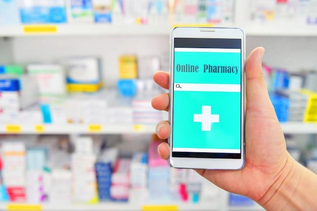 Mano que sostiene el teléfono inteligente móvil para la barra de búsqueda en la pantalla en el fondo de los estantes de la farmacia farmacia. médico en línea.