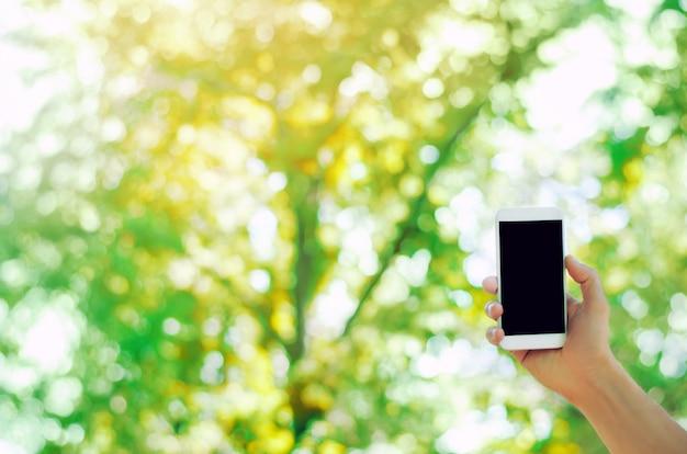 Mano que sostiene un teléfono inteligente móvil en el parque. dependencia telefónica, redes sociales.