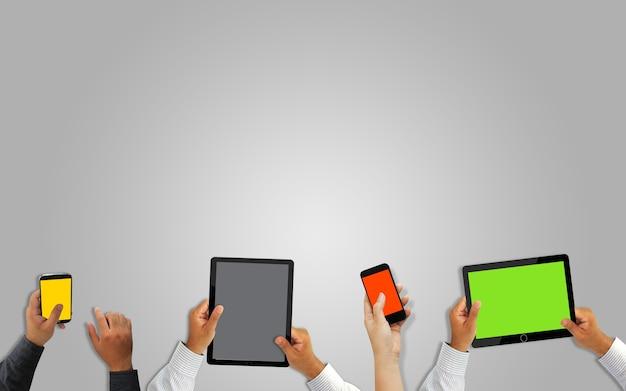 Mano que sostiene el teléfono inteligente móvil y la tableta con pantalla en blanco.