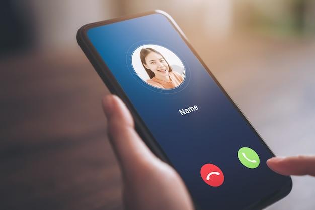 Mano que sostiene el teléfono inteligente y muestra la pantalla de llamada entrante de la niña