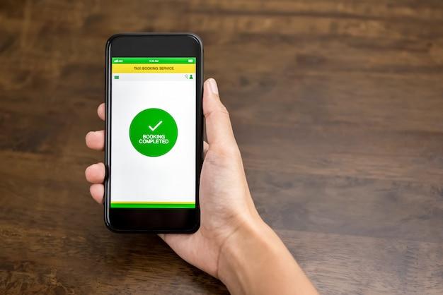 Mano que sostiene el teléfono inteligente que muestra el texto de confirmación en la solicitud de reserva de taxi