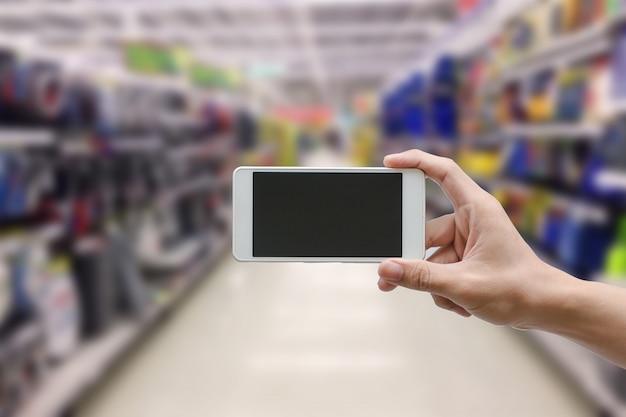 Mano que sostiene el teléfono móvil inteligente con pantalla de monitor en blanco en el supermercado desenfoque, concepto de negocio
